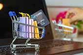 Paper Shopping Bags And Mock-up Of Credit Card In Trolley On Laptop Keyboard. Consumer Can Buy Produ poster