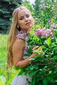 Portrait Of A Charming Blond Woman Wearing Beautiful White Dress Standing Next To Lilac Bush. poster