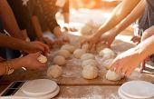 Close-up Hands Forming Dough Balls For Baking Buns On A Wooden Table During Manufacture. Culinary Ma poster