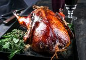 Traditional roasted stuffed Christmas Peking duck with herbs as closeup on a board  poster