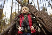 Little Boy Scout With Binoculars During Hiking In Autumn Forest. Behind The Child Is Teepee Hut. Con poster