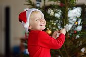 Little Boy Wearing Santa Hat Ready For Celebrate Christmas. Cute Child Decorating The Christmas Tree poster