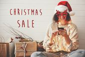 Christmas Sale Text Sign On Stylish Happy Girl In Santa Hat Looking At Phone Screen In Festive Chris poster