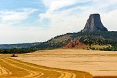 Combine Harvesting Crops Near Devils Tower National Monument (bear Lodge In Native American Culture) poster