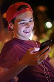 Close-up portrait of a smiling young man with a smartphone, in the street.  Happy teenage boy is usi poster