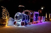 Dimensional Figure A Toy Christmas Locomotive With Cars And Pine Tree, Made Of Multicolored Led Lamp poster