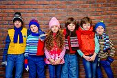 Group of happy joyful children posing together at studio by the brick wall. Kids fashion. Winter cl poster