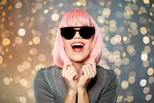 style, fashion and people concept - happy young woman in pink wig and black sunglasses over festive  poster
