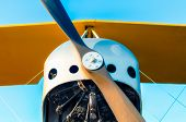 Propeller With Engine And Yellow Wings Of A Vintage Airplane On A Blue Background Close Up poster