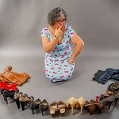 Indecisive Mature Woman Choosing Between Boots Or Heeled Shoes, Group Of Heeled Shoes And Boots In D poster