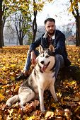 Hipster Stylish Guy With His Husky Dog In Autumn Forest.pedigree Dog Concept. Best Friends. Uncondit poster