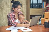Pretty Young Single Mom Working At Home On A Laptop Computer While Holding Her Baby Girl Sitting On  poster