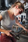 foto of workbench  - Pretty glass sculptor shaping tiny object on workbench - JPG