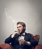 stock photo of mafia  - handsome boss smokes cigar sitting on a red armchair - JPG