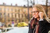 Young woman standing in front of taxi, she gets phone call