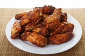 stock photo of mesquite  - A white plate of spicy mesquite flavored chicken wings - JPG