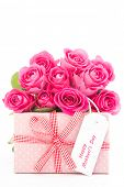stock photo of gift wrapped  - Bouquet of beautiful pink roses next to a pink gift with a happy mothers day card on white background close up - JPG