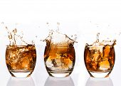 Serial arrangement of whiskey splashing in tumbler on white background