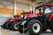 stock photo of workhorses  - Many Tractors on exhibition on big hall - JPG