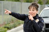 stock photo of lightbar  - a female police officer talks on the radio with her patrol car in the background - JPG