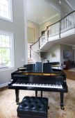 stock photo of grand piano  - grand piano in mansion living room with staircase and large windows - JPG