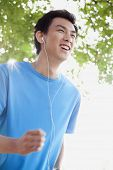 Young man jogging while listening to music