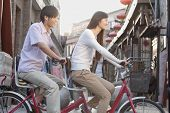 pic of tandem bicycle  - Side view of young couple on tandem bicycle in Beijing - JPG