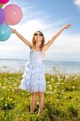 summer holidays, celebration, children and people concept - happy girl waving hands with colorful ba