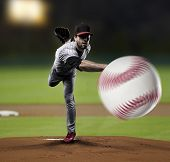 stock photo of ball cap  - Pitcher Player throwing a ball on a baseball Stadium - JPG