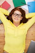 education and home concept - smiling redhead female student in eyeglasses lying on floor with closed