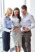business and office concept - smiling business team working with tablet pcs and smartphones in offic