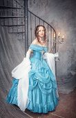 stock photo of medieval  - Beautiful young woman in long blue medieval dress with candelabrum - JPG