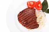italian cuisine : grilled beef steak with pasta and tomatoes on basil leaf on plate isolated over wh