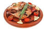 served grilled chicken legs with tomatoes lemon and chives on wooden plate isolated on white backgro