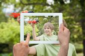 Hand holding tablet pc showing little boy playing with toy airplane in park