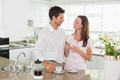 Happy young couple having coffee in the kitchen at home