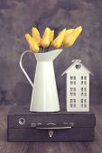 Vintage shabby chic photo of bouquet of spring tulips in a old tin vase on suitcase