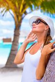 Portrait of pretty woman wearing white hat and sunglasses enjoying bright sun light, happy summer ho