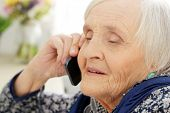 Close-up. Cute, elderly woman with mobile phone