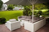 pic of lawn chair  - Modern fashioned patio cafe lounge with umbrella and comfotable chairs in green park - JPG