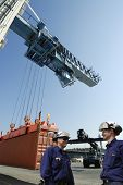 two port workers with cargo containers being hoisted by large crane