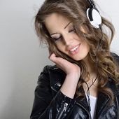 Young beautiful woman with headphones listening music. Teenager girl and music concept. Toned.
