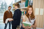 Smiling college student holding books with classmates standing in library