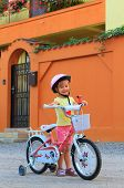 Little girl with bicycle in front of orange house