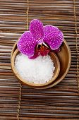 Salt with orchid in bowl on bamboo mat