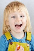 Blond Girl  With Open Mouth Holds A  Felt Pen