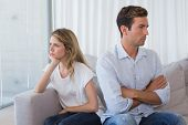 Unhappy couple not talking after an argument in living room at home