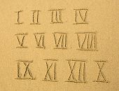 Roman numerals (numbers) written on a sandy beach.
