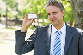 Portrait of confident businessman holding business card in park