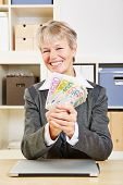 Happy smiling senior business woman with money in the office at her desk